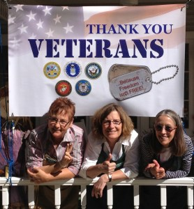 3 Ladies in from of a white flag with Thank you Veterans written on it
