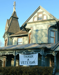B&B with white flag on house with text Thank a Veteran